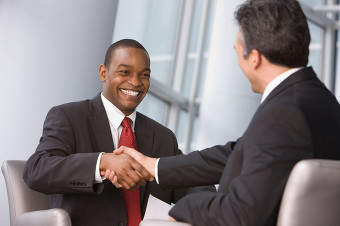 Two men shaking hands at satisfactory outcome